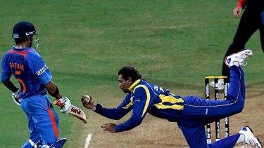 Tillakaratne Dilshan of Sri Lanka dives to take a catch off his own bowling to dismiss Virat Kohli of India.