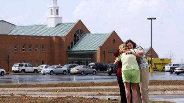 Mourners comfort each other in front of the First Baptist Church in Maryville, Illinois, where a gunman shot dead the pastor and injured several others.