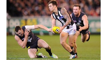 That's got to hurt: Carlton's Mitch Robinson clutches his shoulder as Magpie Jamie Elliott heads upfield.