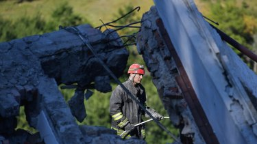 Emergency workers search the rubble of a building.