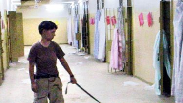 Lynndie England holding a leash connected to a naked detainee at the Abu Ghraib prison in Baghdad.