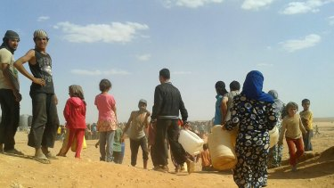 Syrian refugees in June gather for water at the Rukban refugee camp in Jordan's northeast border with Syria.