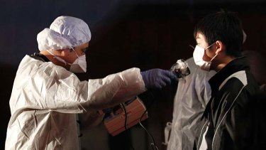 Official in protective gear scans for signs of radiation on a man who is from the evacuation area  near the Fukushima Daini nuclear plant in Koriyama.