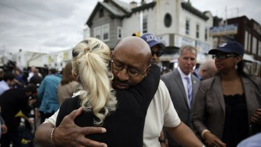 Philadelphia Mayor Michael Nutter, centre right, hugs Lori Dee Patterson, a nearby resident, after she handed him a cup of coffee after he spoke at a news conference.
