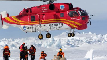 A Chinese helicopter lands on an ice floe next to the Aurora Australis during the Akademik Shokalskiy rescue operation.