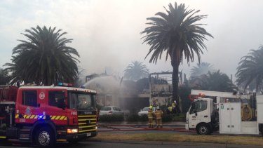 Firefighters douse the burning restaurant with water.