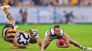 On the deck . . . Hawthorn star Lance Franklin attempts to grab hold of Geelong player David Wojcinski at the MCG yesterday.