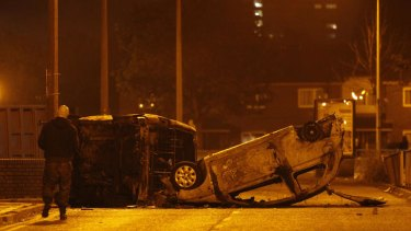 World turned upside down: burnt and upended cars in the aftermath of rioting and arson in Salford, Manchester.
