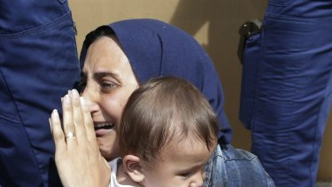 A refugee holding her child is detained in Bicske, Hungary on Thursday.