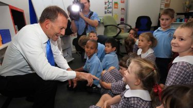 Story time everyone ... Tony Abbott with students at Rosary Primary School in Canberra, where the Leader of the Opposition talked about the wonders of books.