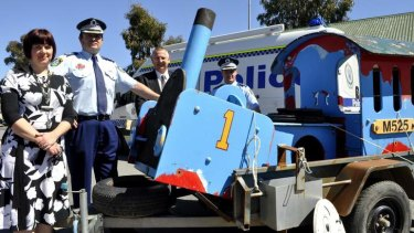 Thomas the Tank Engine is welcomed back to safety by Goulburn Council's Julianne Salway, acting Local Area Commander Evan Quarmby, Mayor Geoff Kettle and Goulburn Police crime manager Detective Inspector Chad Gillies.