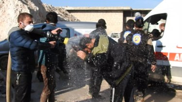 Civil defence workers spray water on victims after the attack.