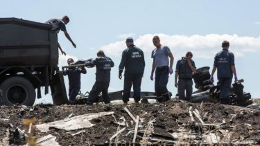 Workers from the Ukranian Emergencies Ministry transfer the bodies of MH17 victims on to a truck on Monday.