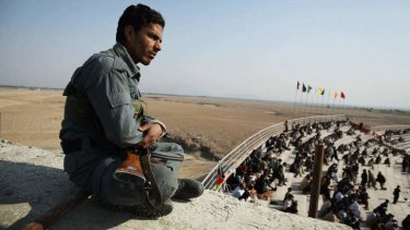 "Close watch: A policeman watches over the crowd at the Tajikistan-Afghanistan ""A"" match in Jalalabad."