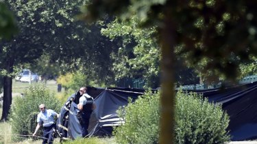 French police erect tents to enclose the area where a decapitated body was found.