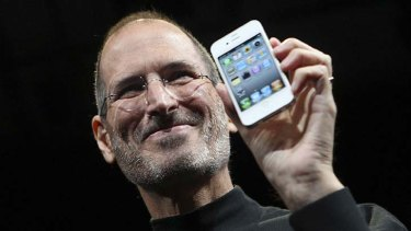 Apple CEO Steve Jobs poses with a white iPhone 4.