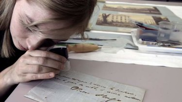Paper conservator Albertine Hamilton studies a Victor Hugo signature which will be included in the State Library's <i>Les Miserables</i> exhibition.