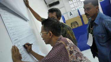 Election officials tally the vote count at a polling station in Jakarta on Wednesday. The result is likely to bring presidential candidate, Jakarta governor Joko Widodo, a step closer to becoming the country's next leader.