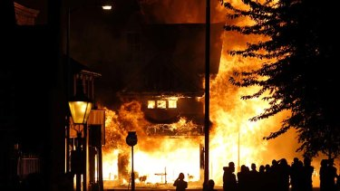 Up in flames ... a shop is set on fire as rioters gather in Croydon, south London.