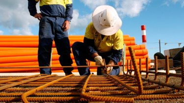 Construction workers prepare concrete reinforcements at a liquified natural gas project.