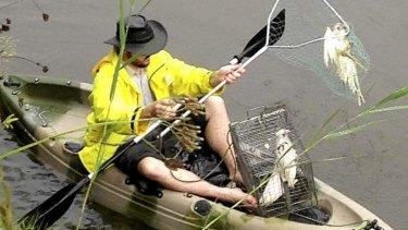 A volunteer plucks out a dead little corella from waters near Dubbo.