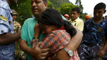 A family member cries after a dead body is recovered from the landslide at Lumle village in Kaski district, close to the nation's most popular trekking circuit.