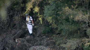 Search ... police scour the bushland under Pheasants Nest Bridge for more human remains.