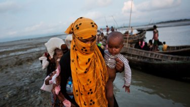 A Rohingya woman carries a child after crossing a stream on a small boat near Cox's Bazar's Dakhinpara area in Bangladesh.