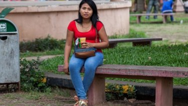 A sex worker sits on one of the benches of Wat Phnom Park, situated in central Phnom Penh.