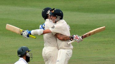 Australian cricketers Mitchell Johnson (left) and Patrick Cummins celebrate victory in the second Test against South Africa at Johannesburg.