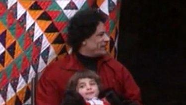 A screenshot from the video showing Muammar Gaddafi cuddling a girl identified as his daughter, 'Hana'.