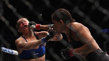 Brazilian Amanda Nunes punches Ronda Rousey in their UFC women's bantamweight championship bout.