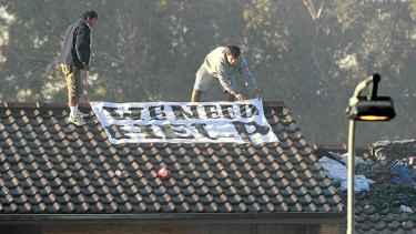 At risk: Protesters lay out a sign on a roof at Villawood detention centre.