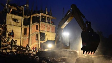 An excavator removes debris as volunteers and rescue workers search the site of a garment factory complex in Bangladesh, which collapsed on April 24.