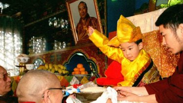Homage ...  Gyaltsen Norbu, installed as the 11th Panchen Lama, is handed rice.