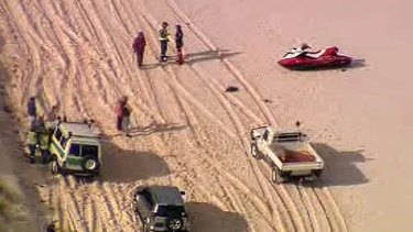 Emergency workers speak with witnesses on the beach. <i>Channel Ten</i>