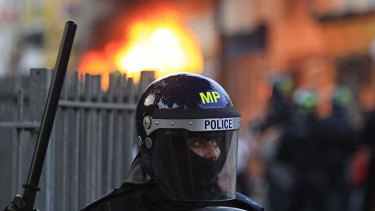 Standing guard ... a police officer wards off rioters in Hackney.