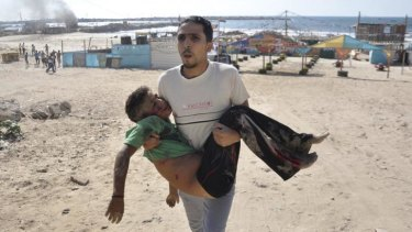 A Palestinian man carries the body of a boy, whom medics said was killed by a shell fired by an Israeli naval gunboat, on a beach in Gaza City.