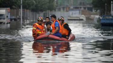 Rescuers use a raft to transport people along a flooded street in Shenyang in north-eastern China's Liaoning Province.
