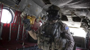 An air crewman from an Australian Army Chinook, based at Kandahar Airfield, uses a control to pick up an American vehicle slung under the aircraft, during a resupply mission to a forward operating base in Afghanistan.
