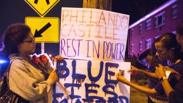 Protesters hang signs near the scene of Philando Castile's shooting.