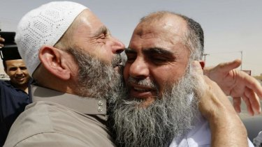 Radical Muslim cleric Abu Qatada (right) hugs his father after being released from a prison near Amman.