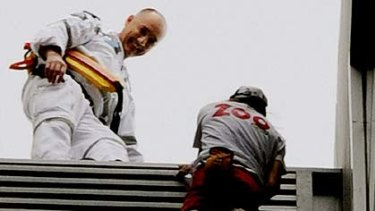 A police officer waits with a smile to take Alain Robert into custody at the end of his 57-storey climb.