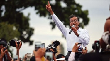 Sam Rainsy, president of the opposition Cambodia National Rescue Party (CNRP), speaks to his supporters after his supporters clashed with policemen, near the Royal Palace in central Phnom Penh September 15, 2013.
