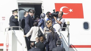 Turkish Prime Minister Ahmet Davutoglu (left) gets into his plane with freed hostages at the airport of the southern Turkish city of Sanliurfa.