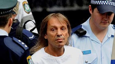 Alain Robert looks wistful after another adventure ends the same way ... in handcuffs.