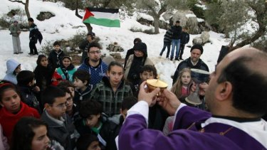 Father Ibrahim Shomali (right), Beit Jala's Roman Catholic parish priest, leads a pre-Christmas celebration in the Cremisan Valley near the West Bank city of Bethlehem.