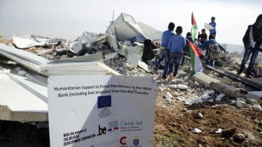 Bedouin children stand amid the rubble of two classrooms demolished by Israeli authorities in the village of Abu Nuwar.