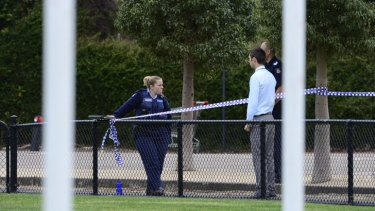 Police at the scene at D.W Nicoll reserve in Oakleigh, where the body was found on a running track circling a football field.