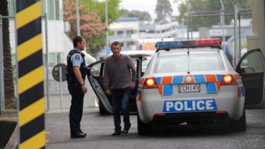 In custody: Phil Rudd, 60, dressed in jeans and a grey sweater, gets out of a police car.